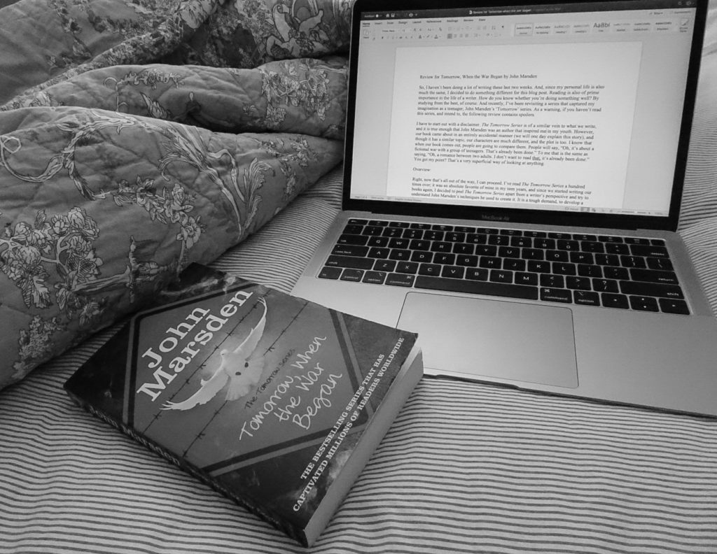 Picture of laptop editing review of book titled Tomorrow When the War Began. The book is closed and sitting beside the laptop and a blanket
