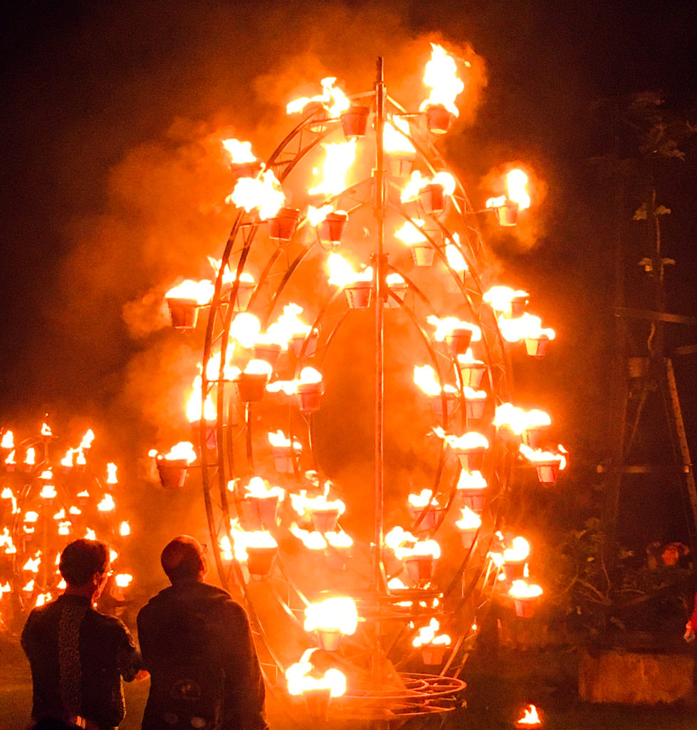 A sculpture with many burning pots of fire, several times as tall as the two silhouetted men standing in the foreground