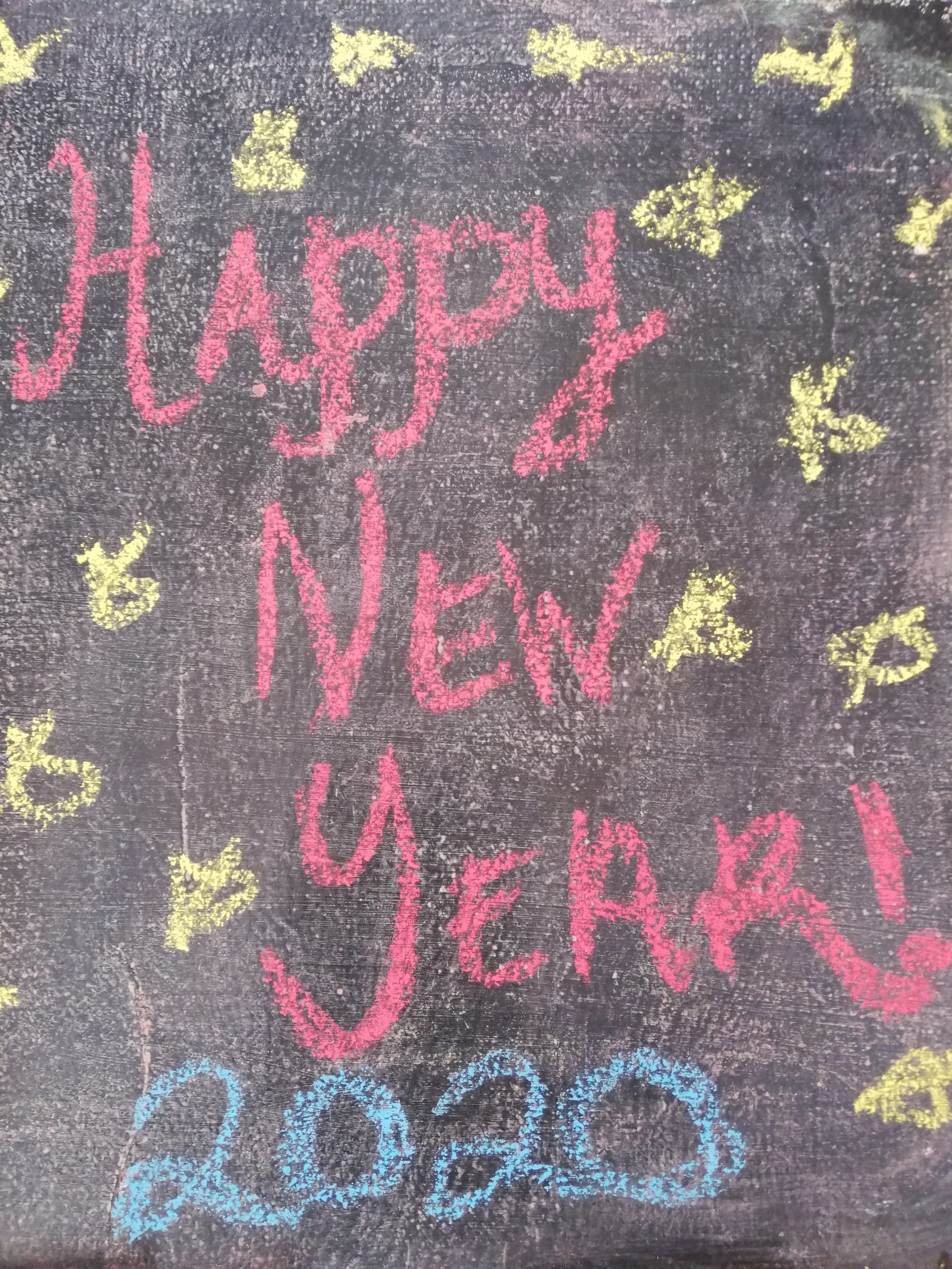 Another decade gone! Picture shows 'happy New Year 2020' in red chalk on the sidewalk with yellow stars