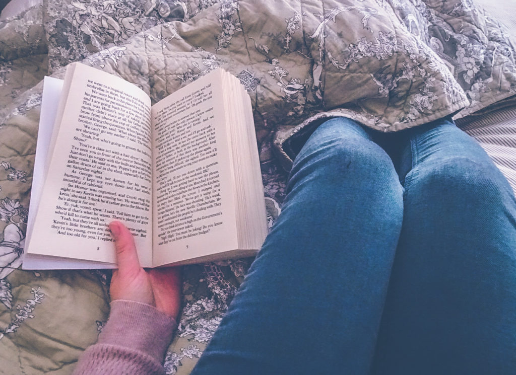 Picture from first person viewpoint, a hand holding the Tomorrow When the War Began book open at the first chapter, legs wearing blue jeans and cuddled with blanket