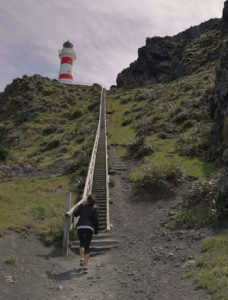 Sometimes all it takes is the first step to get up the mountain. Picture of Ashley finding her motivation as she struggles up some steps towards a red and white light-house.