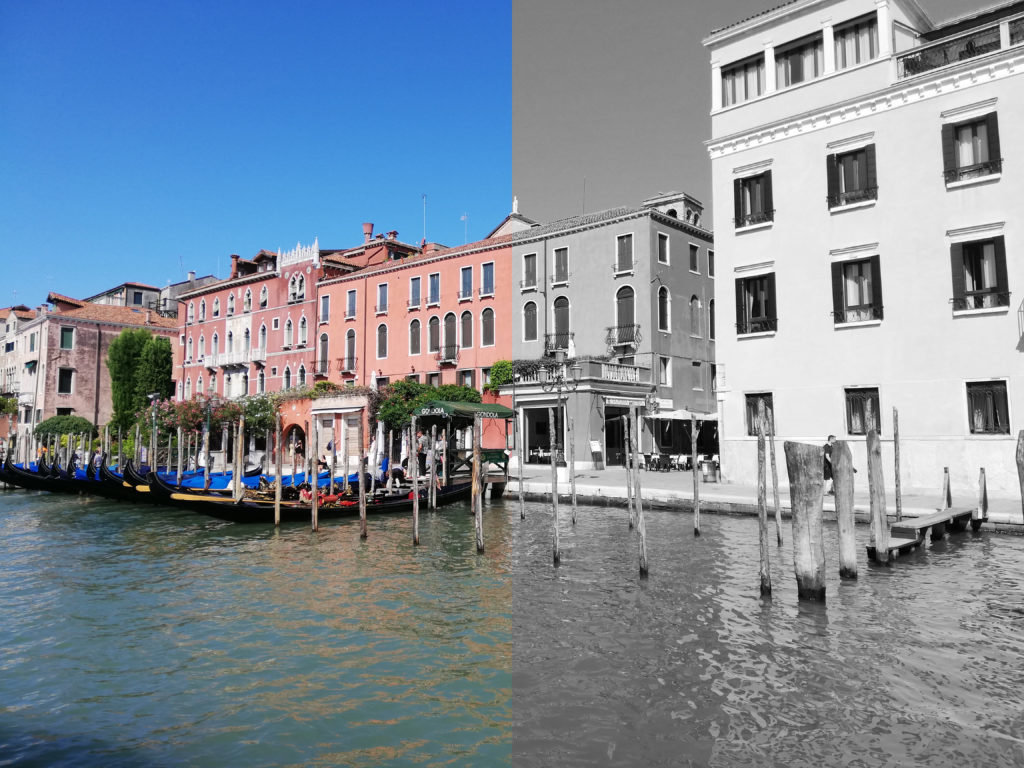 A picture of buildings in Europe along the waterfront. It shows a tale of two chapters, with one half of the picture in color and the other half black and white