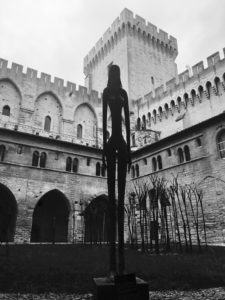Walking on the dark side: an image of a lone female sculpture silhouetted in a courtyard of Avignon castle