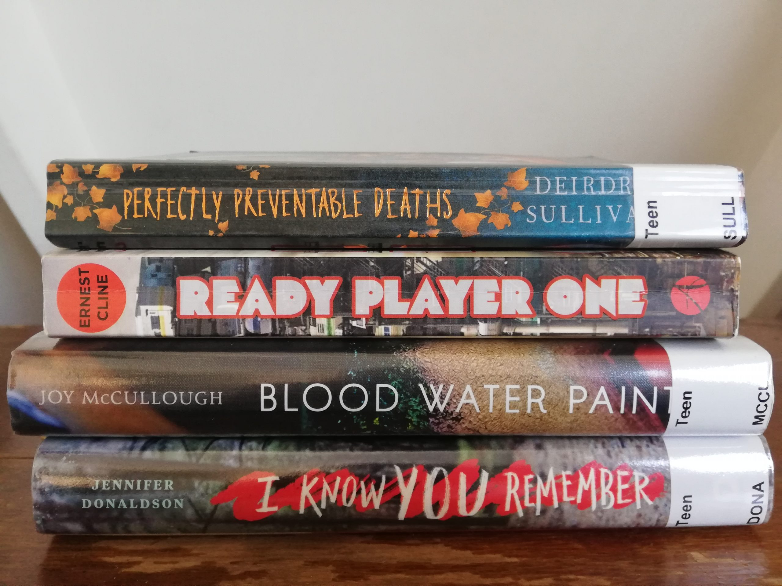 Ashley has plenty of books to read thanks to making a hasty trip to the library before it closed. Titles in the picture include Perfectly Preventable Deaths; Ready Player One; Blood Water Paint; I Know You Remember.