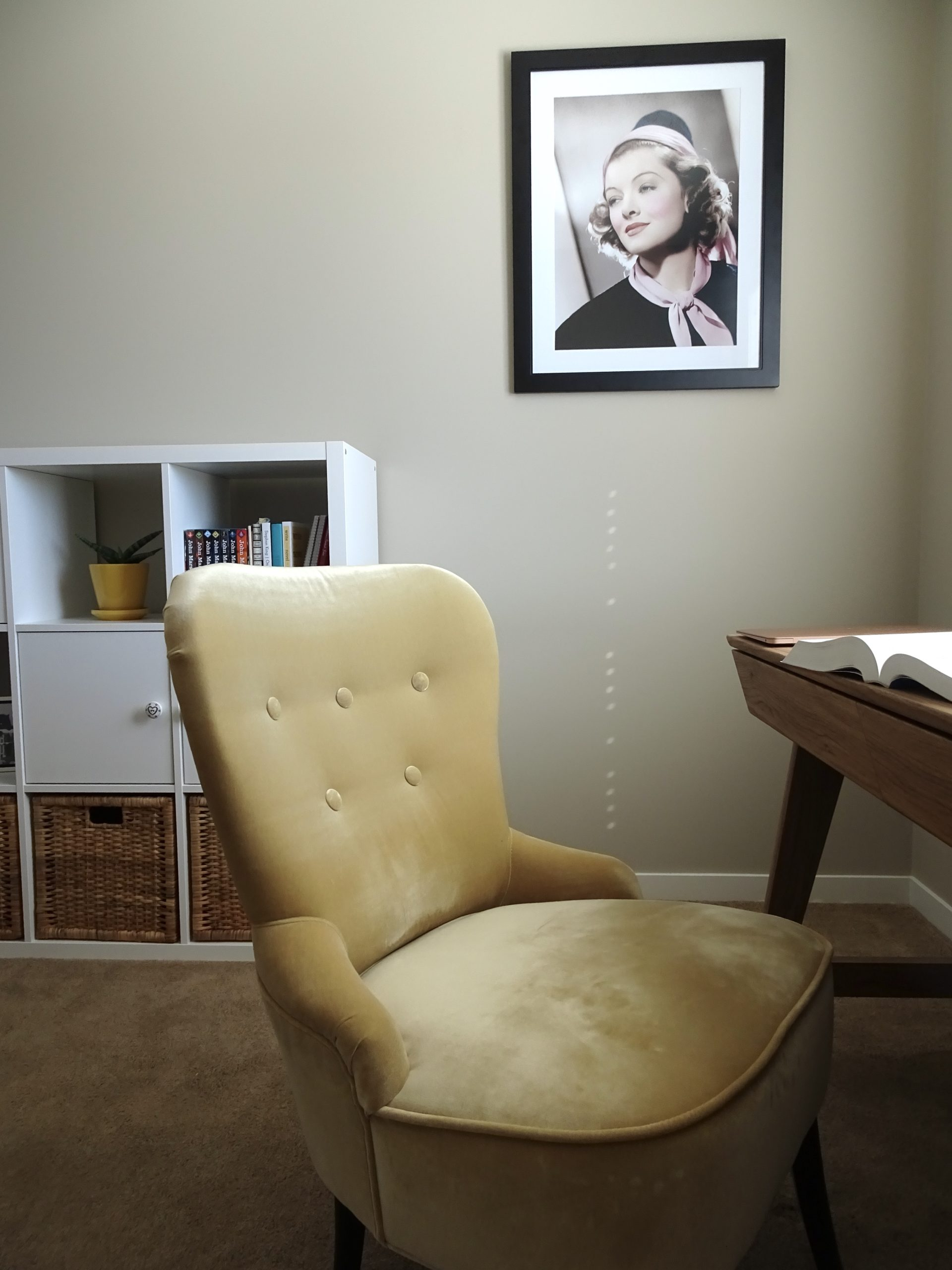 The picture shows Sarah's home office; a pale yellow armchair by an oak-colored wooden desk, with Myrna Loy, the Queen of Hollywood, framed on the wall and a practical-but-pretty white bookcase in the background.