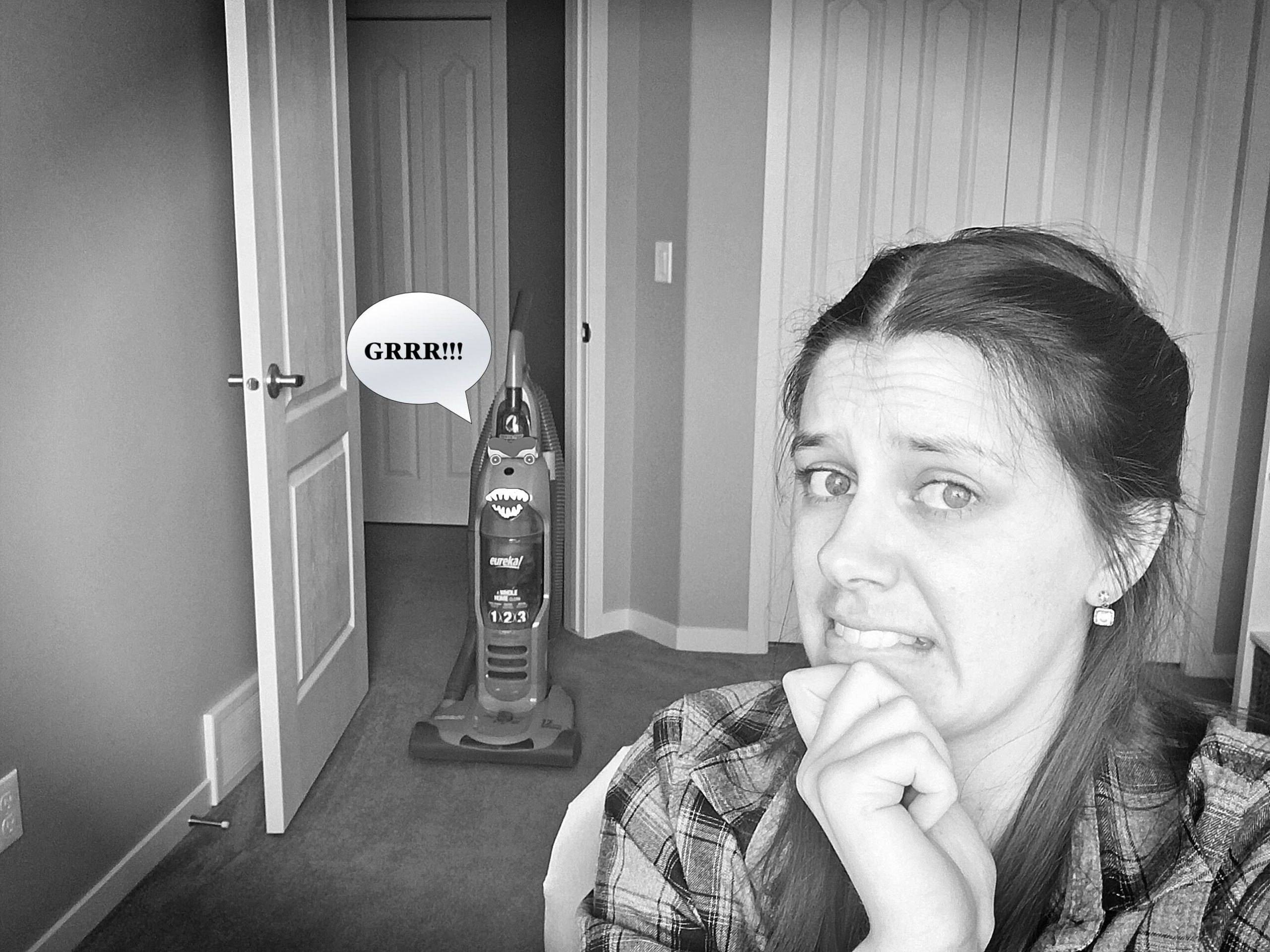 A photo of Sarah sitting at her desk, with an evil vacuum cleaner approaching her from behind and saying the word Grrr! in a speech bubble.