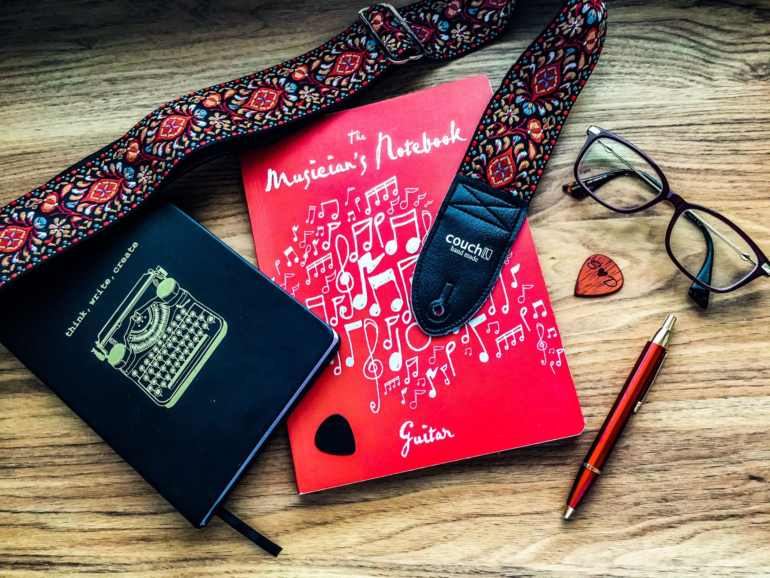 Sarah's creative hobbies keep her busy. And soon, she's about to pick up the guitar again. Picture of her guitar notebook, her writing notebook, a pen, glasses, guitar strap and picks