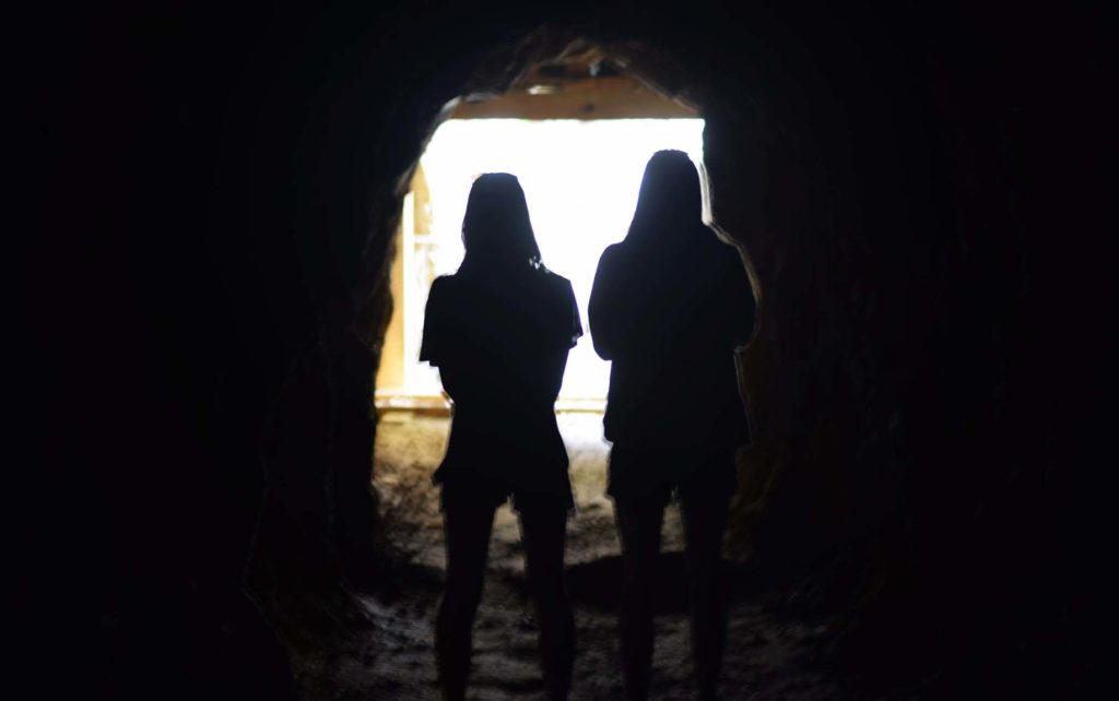 Though Ashley is still in NZ's newest lockdown, there is light at the end of the tunnel. Picture of two silhouetted figures in a tunnel with light streaming in behind them.