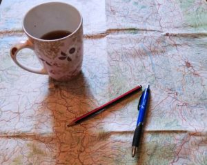 The outline becomes our road map for the novel. Picture of a road map, a pen and pencil, and a mug of tea resting on top