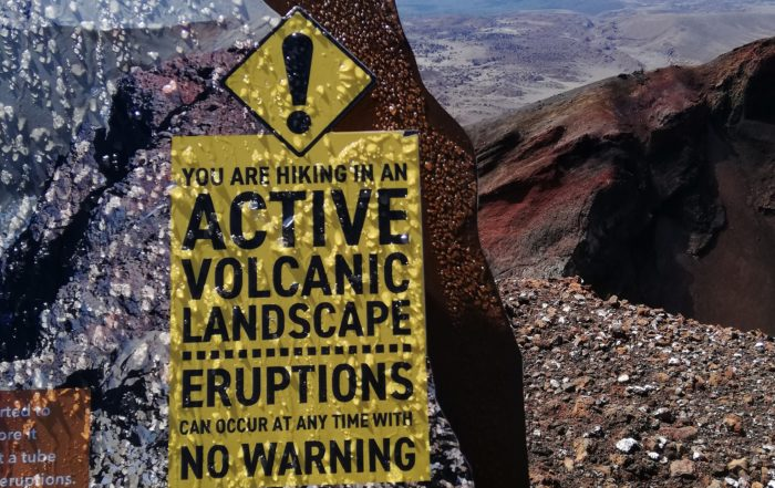 Tongariro has beautiful scenery, and like many of the mountains in New Zealand, is an active volcano. Picture of a yellow warning sign