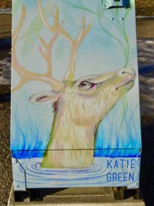 Image of a mural painted on a rubbish bin. A deer is poking its head out of some icy water, with reeds in its mouth.