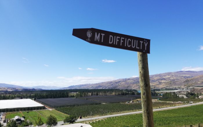 Finding a writing group can be difficult, not unlike this sign post. Photo displaying a signpost to Mt. Difficulty, a mountain on the South Island which is also well known for the prestigious winery there.